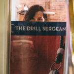 """Woman gazes out from behind a poster with the words """"The Drill Sergeant""""."""